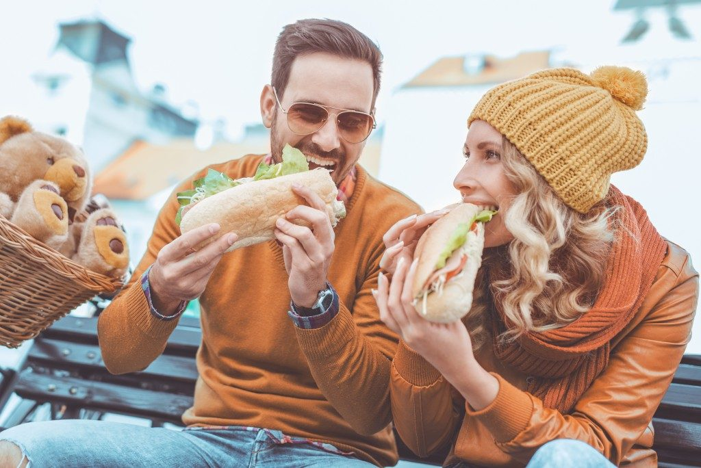 Couple eating a sandwich in the park