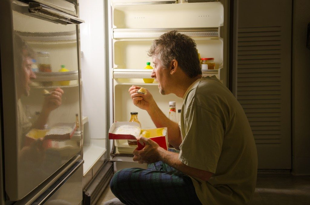 Man eating in front of a refrigerator