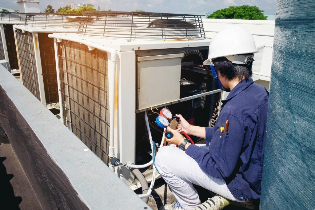person doing maintenance on cooling system of building