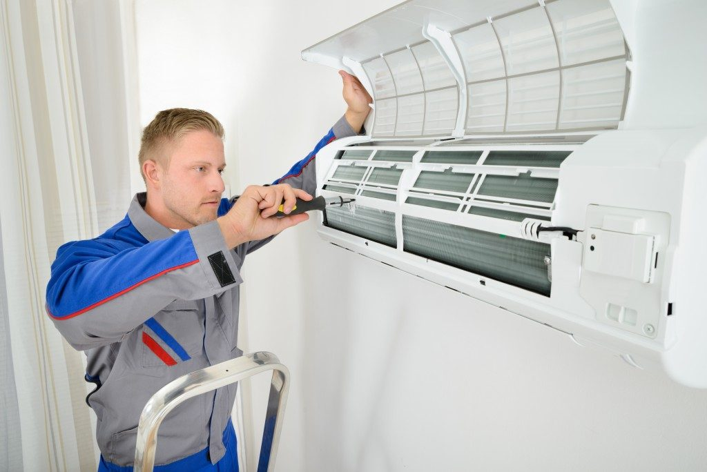 Electrician Repairing Air Conditioner Standing On Stepladder