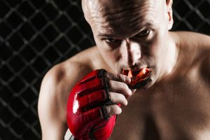 mixed martial artist putting on mouthguard
