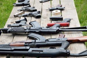 A shotgun, pistols and other firearm are laid out on the table outdoors
