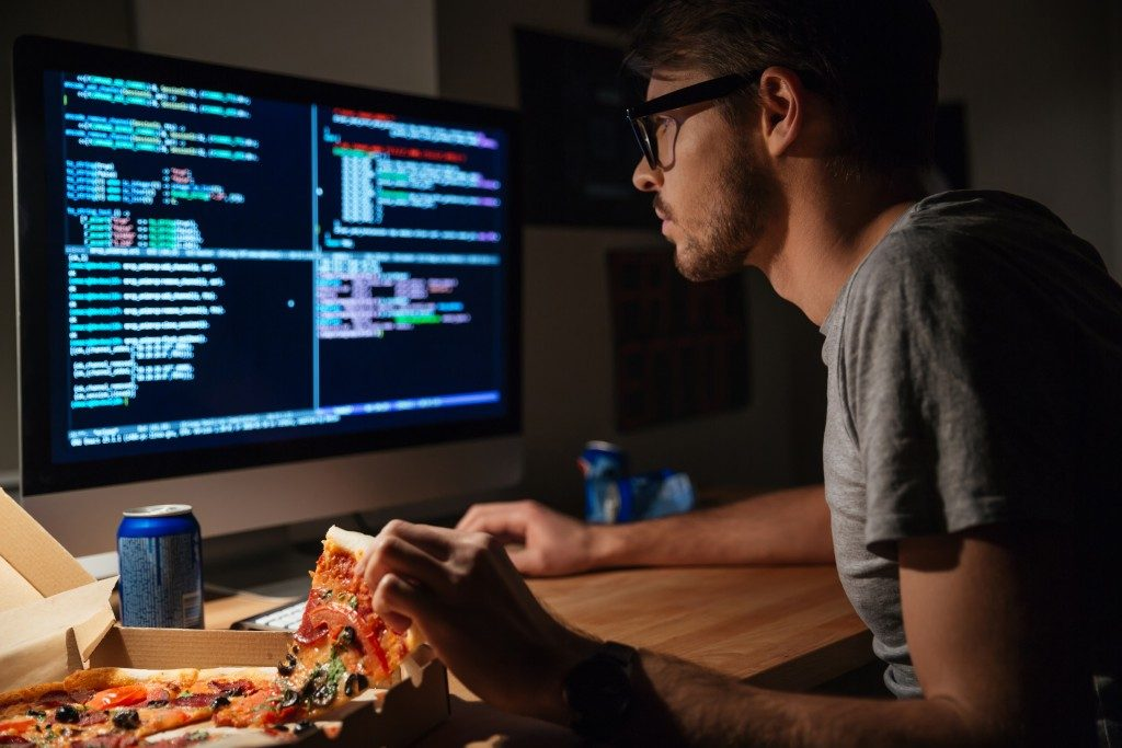 programmer doing coding whilst eating pizza
