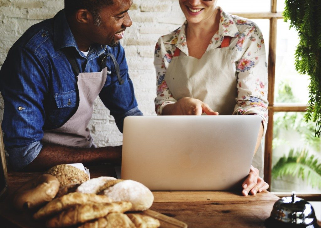 man and woman infront of laptop and bread