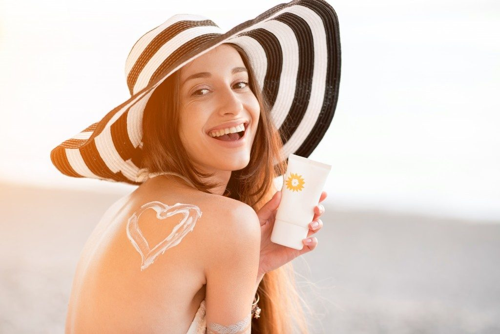 Woman smiling and holding sunscreen