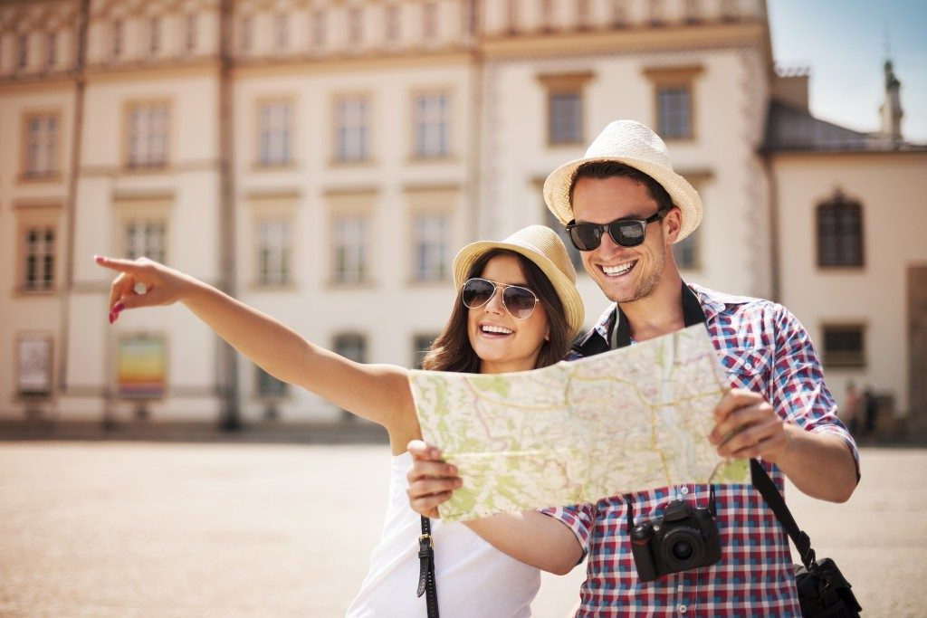 Happy tourists sightseeing wits a map