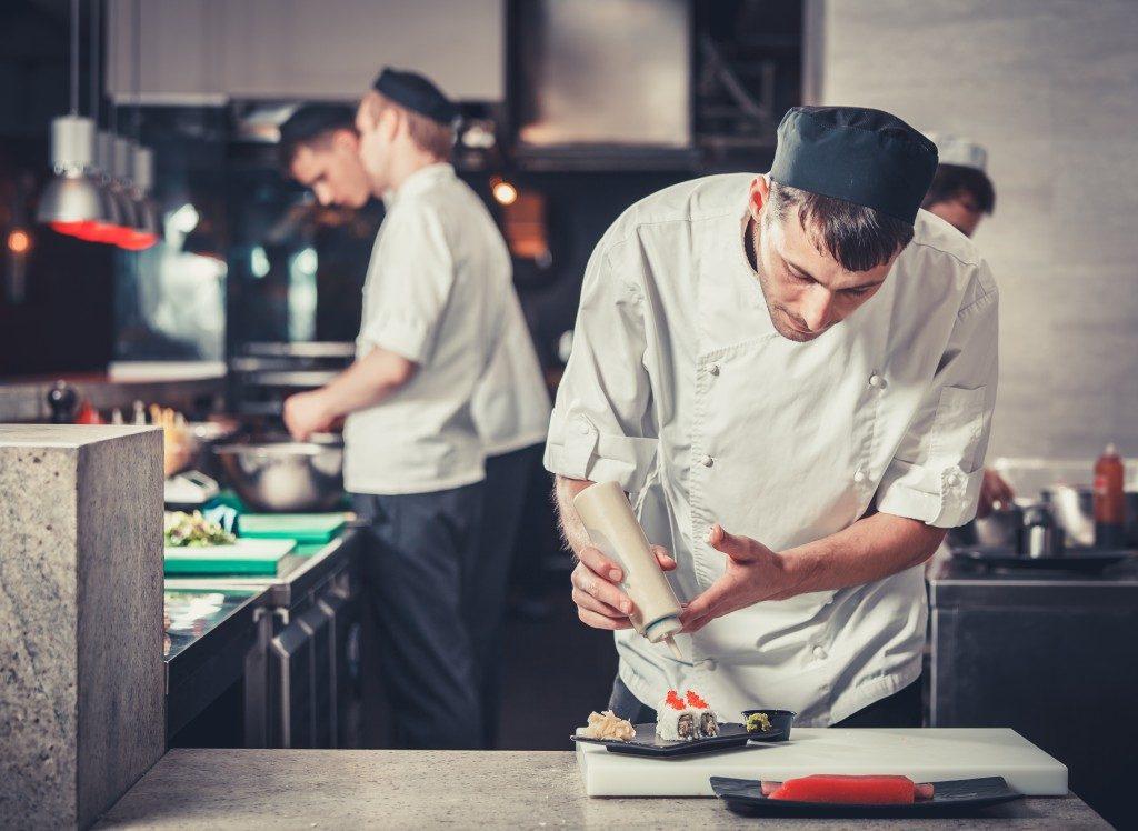 cooks preparing sushi