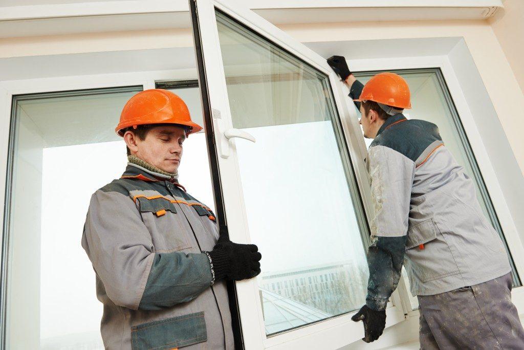 men carrying a glass window