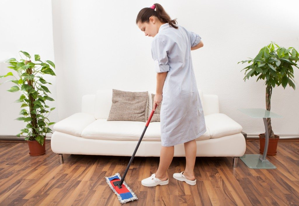 Portrait Of A Young Maid In Uniform Cleaning Floor With Mop