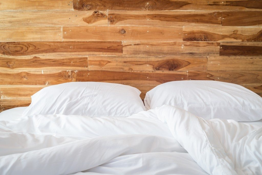 white bedding sheets with wooden headboard