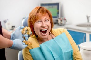 Woman smiling next to her teeth mold
