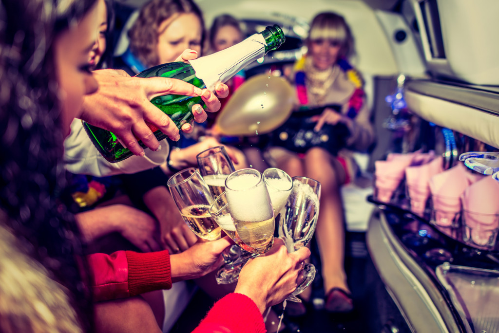 people pouring champagne to their glasses in a party